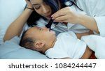 Small photo of Young mother playing with her son by used her hair tickle, little boy feel to titillation and laughing together In leisure time on bed, mother and baby concept