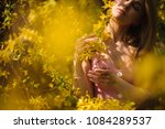 Small photo of Blondie woman, dressed in a chacked top and skirt, standing between branches of yellow blossom tree with closed eyes