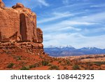 Red rock canyons and snow covered mountains with hazy blue sky - stock photo