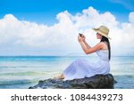 beautiful woman traveler taking photo and enjoying for view of the sea in the morning  on her holiday. Lady tourist in white dress sitting on the rock when the sky are blue.