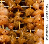 Small photo of kebab marinade chicken meat pepper flavored appetizing bright pieces close-up strung on wooden skewers against grill background