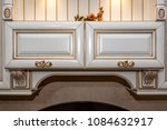Small photo of Front close-up view of classic style white color wooden furniture with gold trim, patina, carving and gilded drawer handle.