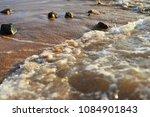 sea beach. stones on sand are... | Shutterstock . vector #1084901843