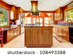 Large red luxury kitchen interior with wood and tiles. - stock photo