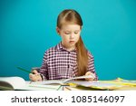 Small photo of Isolated portrait of obedient and diligent schoolgirl doing homework after school. Disciplined child likes to learn.