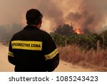 Small photo of A firefighter looks on as a fire approaches Ouranoupoli, Greece on Aug. 9, 2012