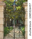 Small photo of Historical wrought iron sward gate protecting the entrance of a colonial mansion and formal mansion