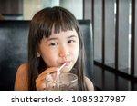asian little girl sipping on a... | Shutterstock . vector #1085327987