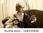 Sepia image of a vintage twenties lady with cocktail and lace fan - stock photo