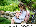 Little girl with pink backpack read using electronic tablet outdoors - stock photo
