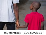 Small photo of father and little son holding hands walking on a road. the father's hand lead his son into the wild with confidence in the outdoors protecting him.the parental concept of parental care. road to life.