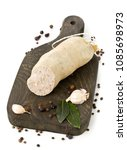 Small photo of German specialty liverwurst (Leberwurst) with spices on wooden board over white background