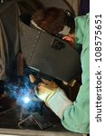 Man working with arc welding equipment/Arc Welder/Blue light from arc welding and a man with protective gear - stock photo