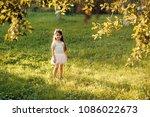 small girl play on green grass... | Shutterstock . vector #1086022673
