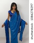 Small photo of Pune, India - June 14 2014: Model poses indoors wearing a saree. The saree is a traditional Indian dress.