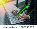Small photo of Investing with laptop online. Stock market concept gain and profits with faded candlestick charts.