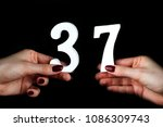 Small photo of On a black background, female hand with number thirty-seven.