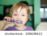 Little child during brushing his teeth - stock photo