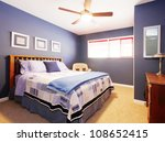 Elegant blue bedroom with yellow carpet. - stock photo