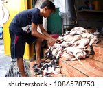 Small photo of ANGONO, RIZAL, PHILIPPINES - MAY 5, 2018: Kitchen workers clean, dress and prepare ducks to be cooked as deep fried ducks, a local delicacy unique to this town which locals and visitors alike love.