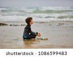 little boy in a surfer suit is... | Shutterstock . vector #1086599483
