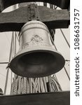 Small photo of Genoa, Italy - May 14, 2017: Bell of the Galleon Neptun old wooden ship in Porto antico in Genoa, Italy. Black and white photography sepia toned.