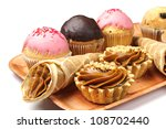 Cakes and cupcakes on a plate on white - stock photo