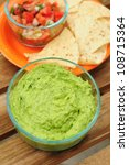 Bowl of guacamole made from fresh avocados, chips and salsa - stock photo