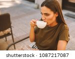 young woman drinking coffee in... | Shutterstock . vector #1087217087