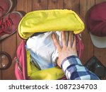 hand packing clothes in the... | Shutterstock . vector #1087234703