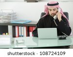 Portrait of a smart arabic business man using laptop and talking  on the phone - stock photo