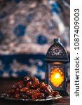 Small photo of The Muslim feast of the holy month of Ramadan Kareem. Beautiful background with a shining lantern Fanus and dried dates on wooden boards. Free space for your text
