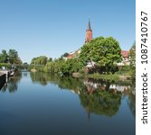 Small photo of St. Marien Andreas Church in Rathenow in Springtime with the Havel River in the foreground