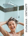 Happy woman applying shampoo in shower - stock photo