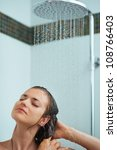 Relaxed woman taking shower under water jet - stock photo