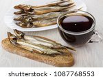 Small photo of Sandwich with smoked capelin, capelin in dish and cup of kvass on wooden table