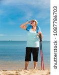 Small photo of Senior woman practicing nordic walking on sea shore, drinking fresh water after activity. Elderly female enjoying sunny summer day. Healthy active retirement age.
