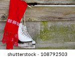 ice skates with bright red scarf hanging on wood siding - stock photo