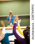 group of students arms up in classroom - stock photo
