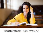 beautiful female college student sitting in classroom - stock photo