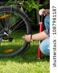 Small photo of Closeup photo of man connecting air pump to valve on bicycle wheel