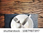 dirty plate with silver knife... | Shutterstock . vector #1087987397
