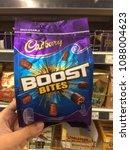 Small photo of Subang Jaya, Malaysia - 7 May 2018 : Hand hold a boost chocolate bites packet brand CADBURY in the supermarket.