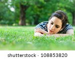 Young woman relaxing and listening to music outdoors - stock photo