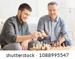 mature man playing chess with... | Shutterstock . vector #1088995547