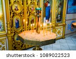 Small photo of Holy Hand, Russia - June 24, 2017: Orthodox church from the inside. Burning wax candles in front of icons and frescoes. Christian religion.