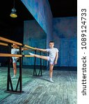 Small photo of boy ballet dancer doing exercise at dance class near the barre indoors