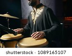 Small photo of Man hands playing music at djembe drums. Musician playing congas, close-up. Rhythm of Africa, Bongo drum music