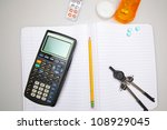 Studying into Oblivion/Calculator, pencil, pills, compass arrayed over collegiate notebook - stock photo