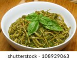 Basil Pesto over Linguine Pasta in White Bowl. - stock photo